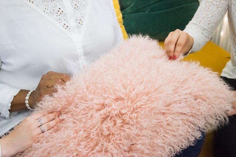 Clientes touchant le coussin en poils d'agneau rose Les Décos d'Axelle